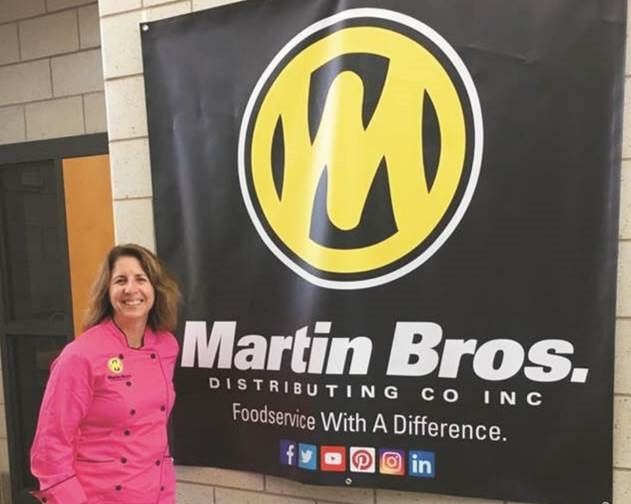 Instructor Diane Stanely standing next to Martin Bros. Sign