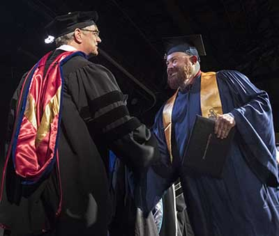 Adult graduate receiving diploma