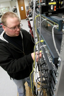 Student working in computer lab on routers.