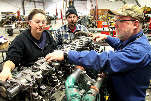 To diesel students working on an engine with the diesel technology instructor