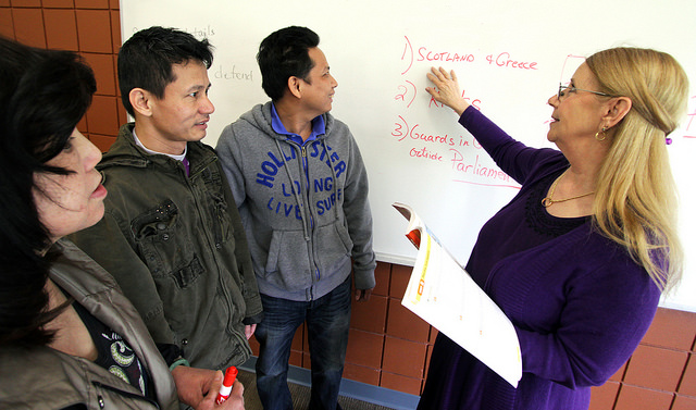 Teacher instructing students at a whiteboard
